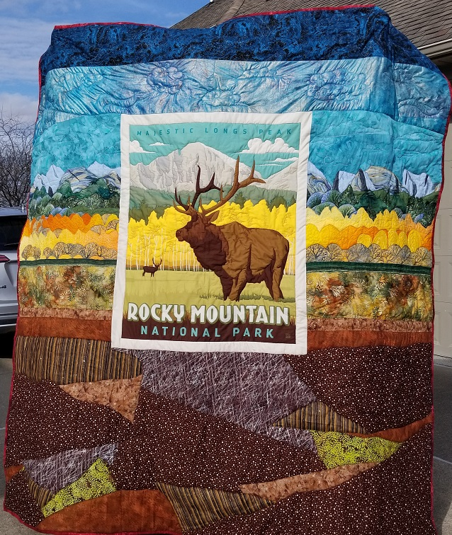 The panel from the first picture set in a quilt, where the image continues to the edges - blue sky, at the top, then a row of mountains, a row of dark green pine trees, a row of yellow aspen trees, grassy meadow, a small deer in the background and large elk in the foreground, bottom portion is large blocks of various brown and green fabrics in irregular wedges layered on each other.